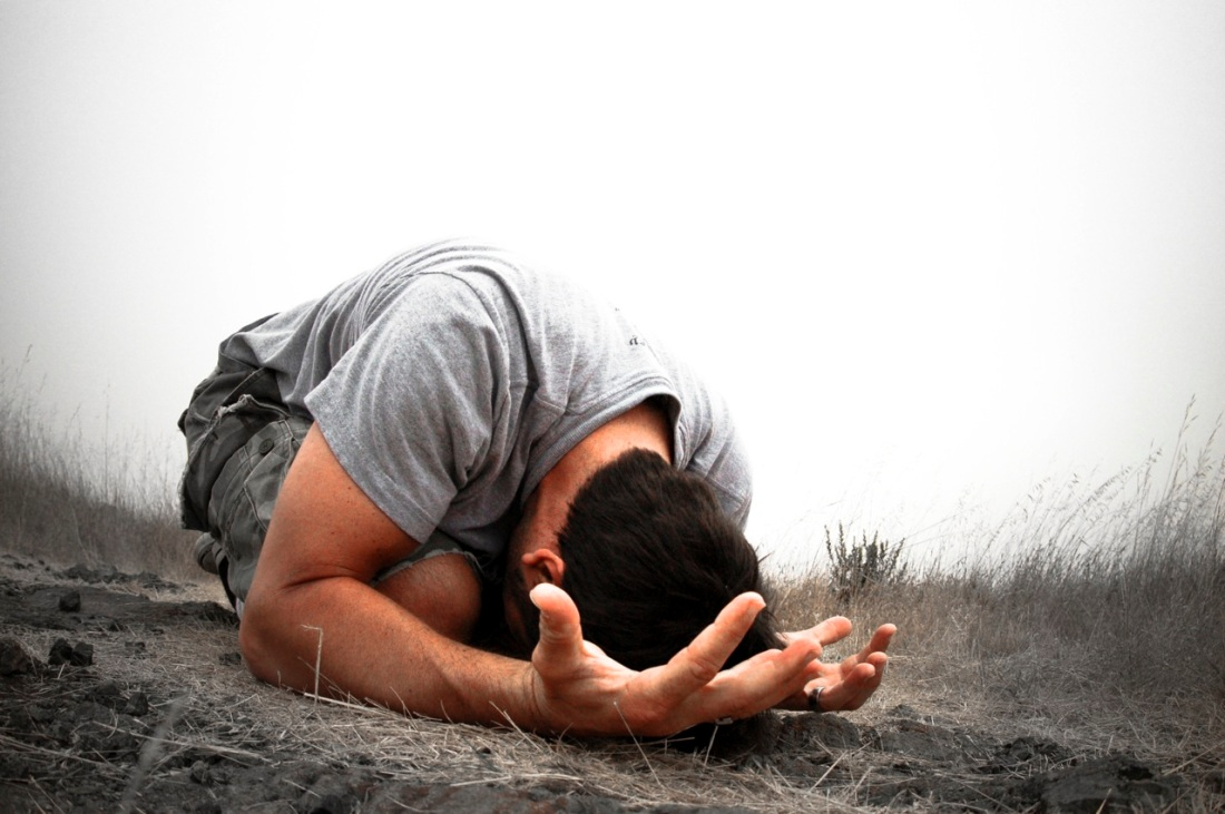 man praying on ground