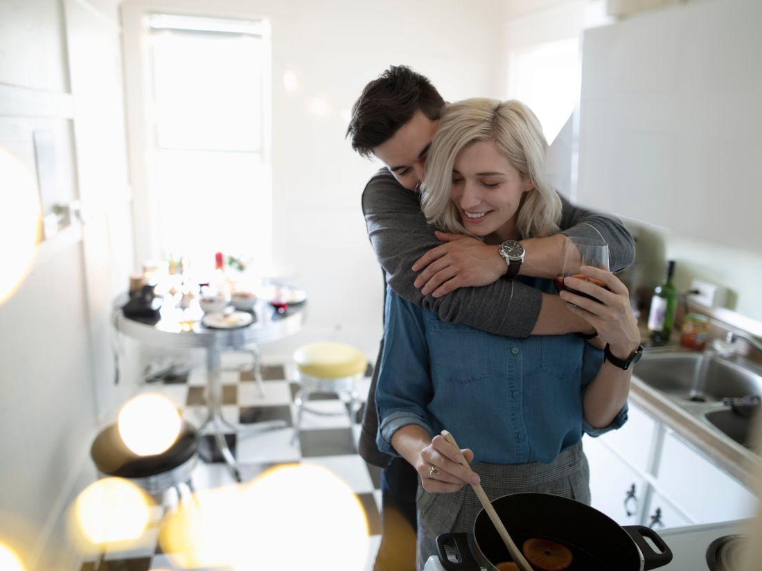 affectionate-young-couple-hugging--cooking-in-apartment-kitchen-1014367764-5c12cdaa46e0fb00012a9092